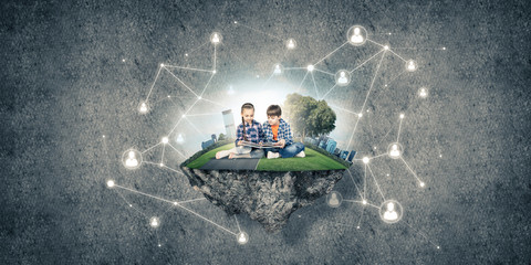 Two kids of school age with book exploring this great world