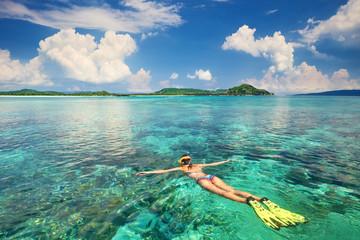 Kobieta z rurką w czystych wodach tropikalnych na tle egzotycznych wysp.