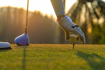 Wręcza azjatykciej kobiety kładzenia piłkę golfową na trójniku z klubem w polu golfowym na wieczór i zmierzchu czasie a dla zdrowego sporta. Koncepcja stylu życia.