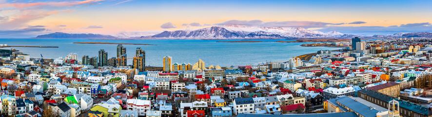 Powietrzna panorama w centrum Reykjavik przy zmierzchem z kolorowymi domami i śnieżnymi górami w tle