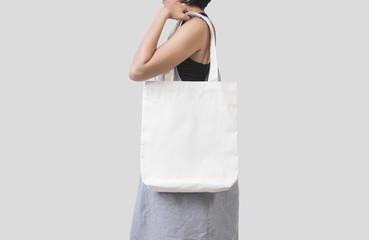 Dziewczyna trzyma torby płótno tkaniny dla makieta pusty szablon na białym tle na szarym tle.