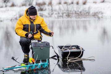 Mężczyzna lodowy połów na zamarzniętym jeziorze.