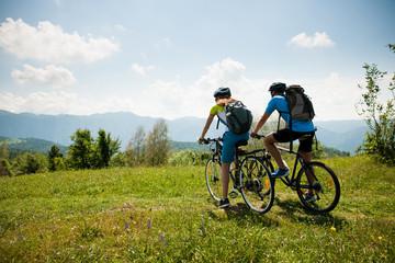 AKTYWNE Młoda para na rowerze po leśnej drodze w górach w wiosenny dzień