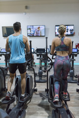 TV training Couple training in elliptical bike while watching tv