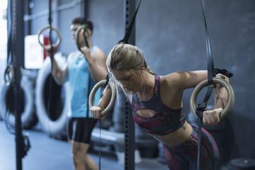 Trening ringowy, kobiety trenujące pierścień olimpijski w pokoju crossfit z mężczyznami