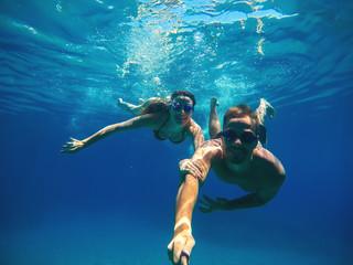 Podwodne selfie z kijem szczęśliwej przystojnej pary miłosnej pływającej w turkusowym morzu pod powierzchnią na letnie wakacje.