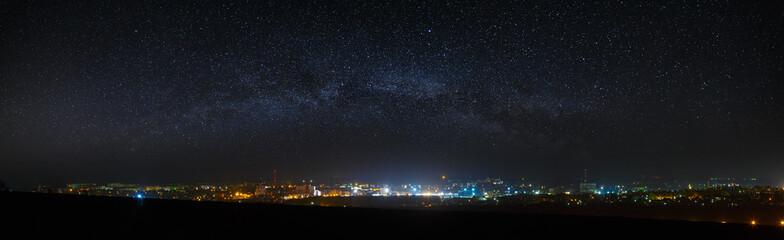 Panoramiczny widok na rozgwieżdżone niebo nad miastem.