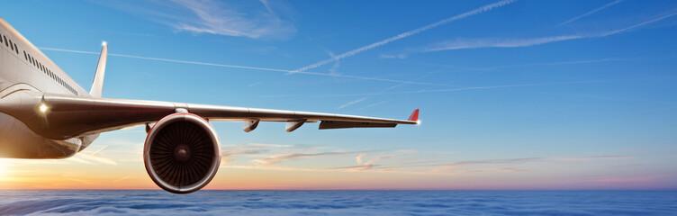 Szczegół skrzydło handlowy odrzutowy samolotowy latanie nad chmury w pięknym zmierzchu świetle.