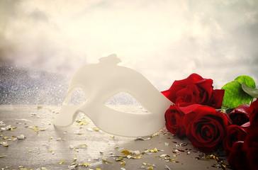 Image of elegant venetian mask on red silk and glitter shiny background.