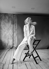 High Fashion blond woman in white suit. Elegant Style model. Dynamic shot in Photo studio shooting