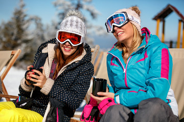 Girls friends enjoying hot drink in cafe at ski resort. Sunbathing in snow