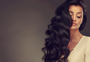 Brunette  girl with long  and   shiny wavy hair .  Beautiful  model woman with curly hairstyle .