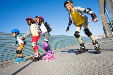 Happy kids rollerblading on the road at sunny day