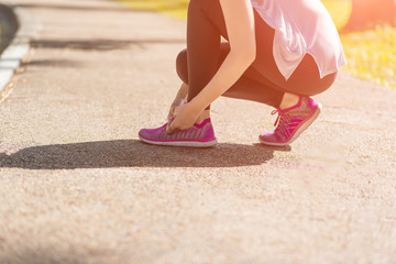 Sport woman in sportswear lacing sport footwear for running in the park. Healthy lifestyle and sport concept.