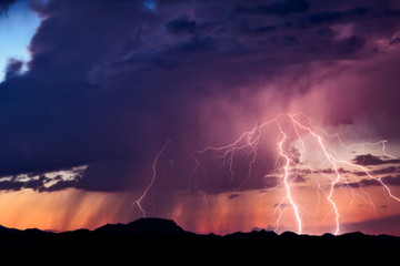 Lightning strikes from a monsoon thunderstorm at sunset in the Arizona desert.