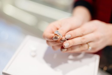 Female seller in a luxury jewelry store presents a ring.