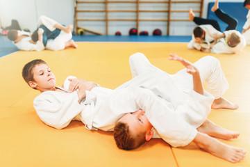 Chłopcy w mundurach ćwiczą sztukę walki