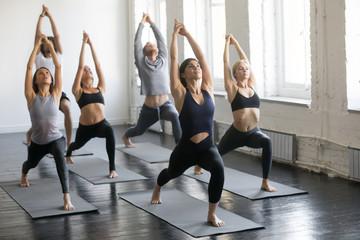 Grupa młodych sportowców ćwiczących lekcje jogi z instruktorem, rozciągających się w ćwiczeniu Warrior One, pozy Virabhadrasana 1, ćwiczących, kryty pełnej długości, studio