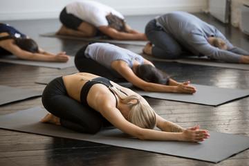 Grupa młodych sportowców ćwiczących lekcje jogi z instruktorem, rozciągających się w ćwiczeniach dla dzieci, pozy Balasana, ćwiczeń, zbliżeń w pomieszczeniu, studentów trenujących w klubie, studio