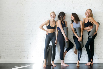 Group of young sporty girls with yoga mats standing at white wall. Female companions in gym resting after fitness, indoor full length, loft studio, copy space