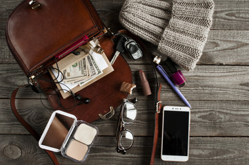 brown open bag with various female accessories, knitted hat, smart phone, dollars, flat lay on wooden boards.