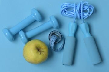 Jump rope, fruit, measure tape and barbells, topview