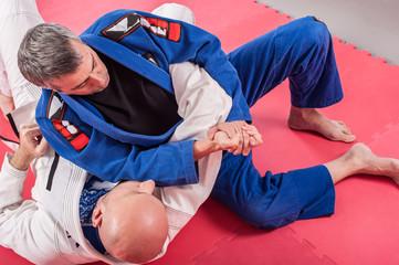 Brazilian jiu jitsu instructor demonstrates ground fighting arm lock techniques