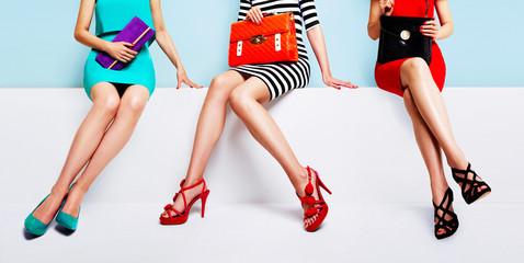 trzy kobiety z pięknymi butami i torbami siedzące razem na ławce.