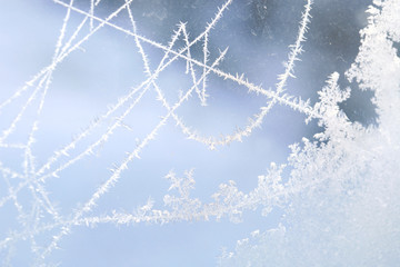 Ice patterns on the window during strong frost. Flowers, lines, crystals, ice rose, abstract pattern