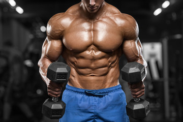 Muscular man working out in gym doing exercises with dumbbells, strong male naked torso abs