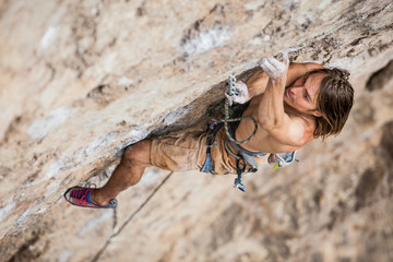 shirtless male climber working hard to lead up a rock wall