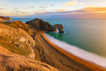 Gorgeous golden light at the famous Durdle Door on the Jurassic Coast, Dorset, UK.