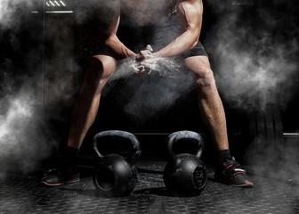 Sztangista klaska w dłonie i przygotowuje się do treningu na siłowni