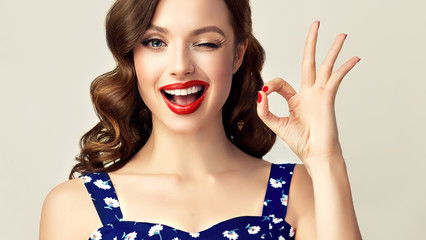 Pin-up retro girl with curly hair  winking, smiling and showing OK sign . Presenting your product. Expressive facial expressions