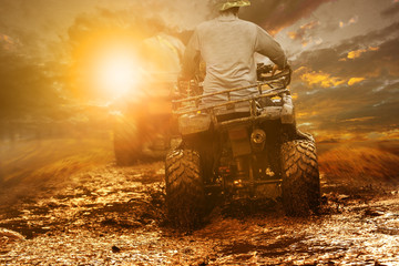 man riding atv through mud terrain field