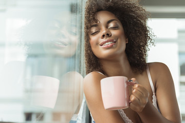 Portrait of cheerful african woman expressing pleasure while drinking cup of delicious beverage in room