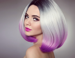 Bob hairstyle. Colored Ombre hair extensions. Beauty Model Girl blonde with short purple hair style isolated on gray background. Closeup woman portrait.