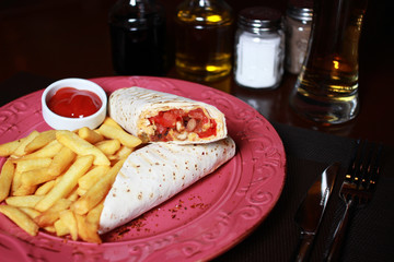 Burrito with French fries, beer, ketchup,  fork, knife on the red plate and napkin.
