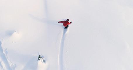 Snowboard widok z góry na dół na snowboardzistę jadącego przez świeży proszek Snow Down Ski Resort lub stok backcountry - tło sportów ekstremalnych