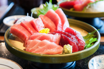 Close up shot of Fresh salmon, tuna, toro, maguro, otoro sashimi with wasabi on ceramic plate