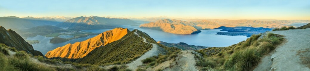 Breathtaking, Stunning Panoramic Landscape View from Roys Peak on Lake Wanaka with golden sunshine light at twilight, South Island, New Zealand.