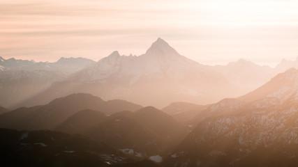 Berge in dunstigen Sonnenstrahlen an einem Abend im Winter