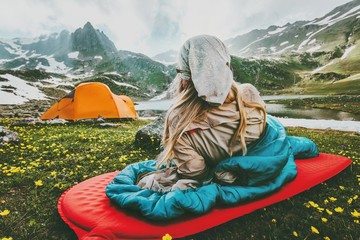 Woman relaxing in sleeping bag on red mat camping travel vacations in mountains Lifestyle concept adventure weekend outdoor wild nature