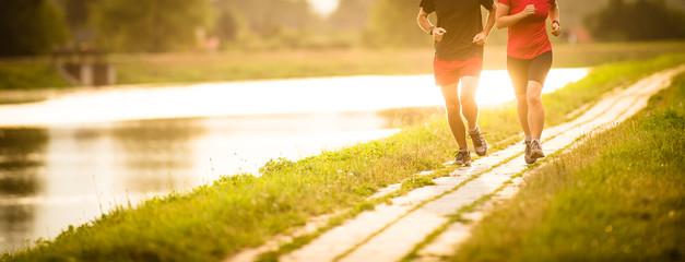 Para biegnie na zewnątrz, o zachodzie słońca, nad rzeką, pozostając aktywnym i sprawnym