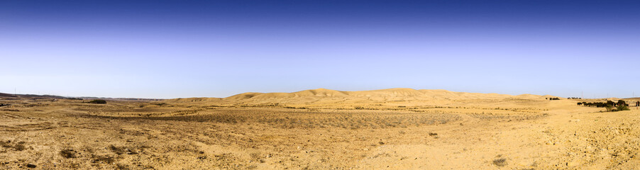 Wery wide panorama of desert hills under blue sky