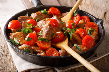 Stewed beef in spicy sauce with tomatoes and greens close-up. horizontal