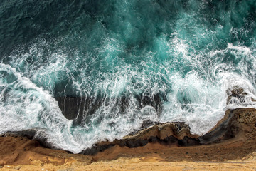 aerial view of ocean waves on cliff
