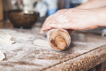 Female hands roll out dough with wooden rolling pin