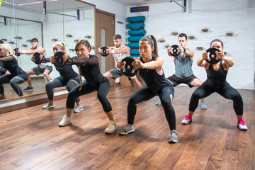 Group of sporty women and men exercising together with weight plates in health club.