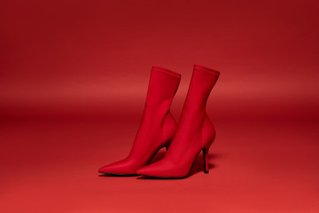 Pair of red high-heel shoes on the deep red background
